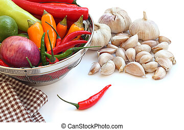 vegetables in metal colander and garlic on white background