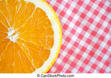 Half orange on red checkered tablecloth