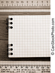 checked note paper on wooden background
