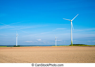 Windwheels behind a barren field - Three windwheels standing...