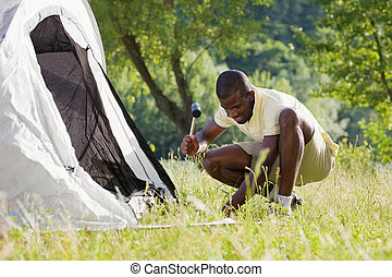 man camping - Young afro-american man fastening tent and...