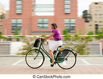 female commuter cycling - mixed-race businesswoman going to...