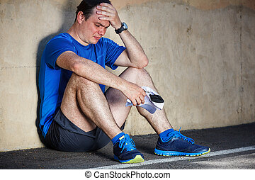 Upset Young male runner resting leaning against wall