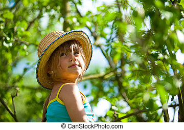 Little beautiful girl posing in a straw hat in the park.