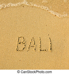Bali - written in sand on beach texture - soft wave of the sea.