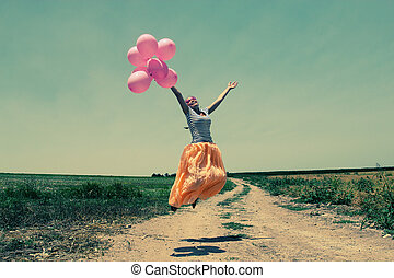 Young woman holding pink balloons and flying over a meadow....