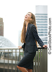 Business woman laughing in the city - Portrait of a business...