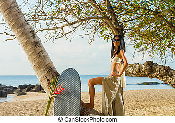 Woman in sarong relaxing by the coconut tree - Woman in...