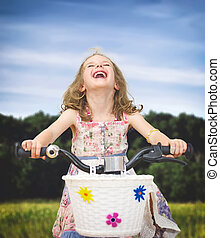 Happy little girl on a bicycle in the park.