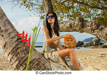 Woman in sarong relaxing by the coconut tree in Thailand