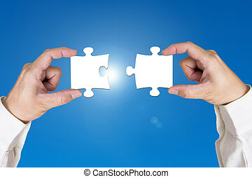 Assembling two blank puzzles together sunny sky background