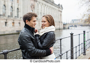 Romantic Couple In Jackets Embracing By Railing - Side view...