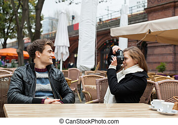 Woman Photographing Man At Outdoor Restaurant