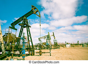 Oil and gas industry. Pump jack on a sky background. Toned.