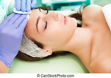 face treatment - woman at facial cosmetics treatment