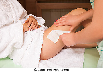 waxing legs - woman at cosmetics salon waxing legs