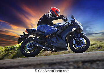 young man riding motorcycle on curve of asphalt country road...