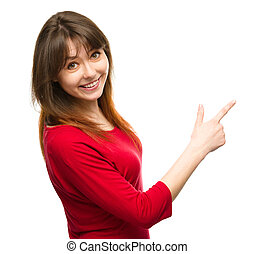 Portrait of a young woman pointing to the right using her...
