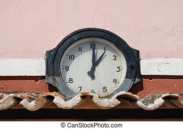 Ancient clock above roof tiles (1 o\'clock)
