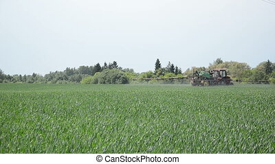 crops fertilizing - tractor with nozzles fertilizing grown...