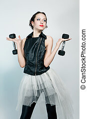 Beautiful fashion model posing with two dumbbells