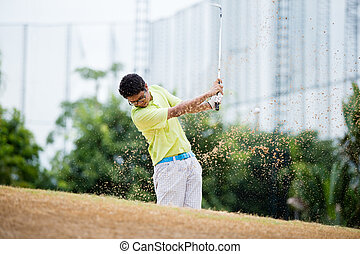 Male golfer hitting golf ball out of a sand trap with sand...