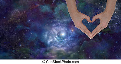 Loving the Universe - Female hands forming heart shape laid...