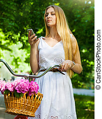 Beautiful blond woman wearing a nice dress having fun in park wi