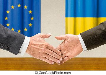 Representatives of the EU and Ukraine shake hands