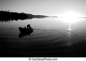 Pacific Northwest Sunset - A man in a boat at Cline Spit in...