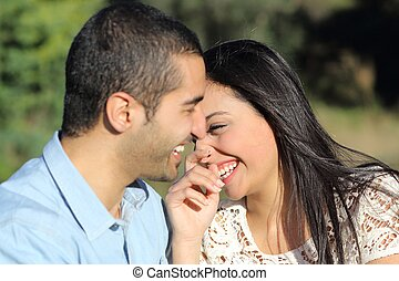Arab casual couple man and woman flirting and laughing happy in a park