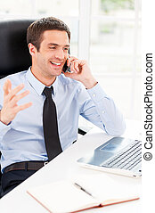 Happy businessman. Happy young man in formalwear looking at computer monitor and talking on the mobile phone while sitting at his working place