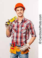Confident contractor. Handsome young handyman with tool belt...