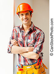 Confident repairman. Handsome young handyman in hardhat...