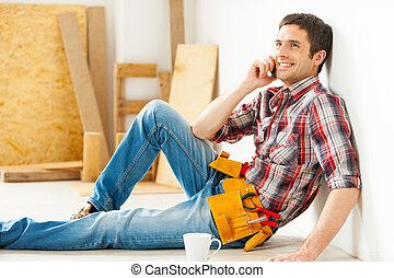 Handyman relaxing. Handsome young handyman talking on the...