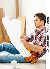 Examining blueprint. Confident young handyman examining blueprint while sitting on the floor