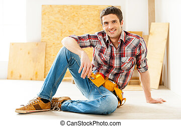 Handyman relaxing. Handsome young handyman in talking on the...