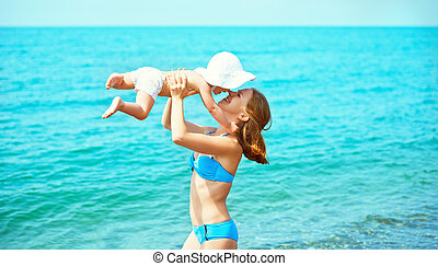 happy family on the beach mother throw up baby daughter and...