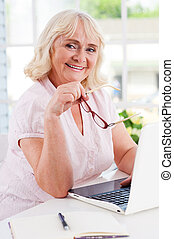 Feeling young and energetic. Happy senior woman using laptop and smiling at camera while sitting at the table