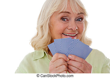 I am winning Happy senior woman holding playing cards and...