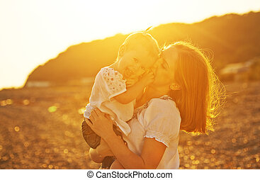 happy family. Mother and baby girl daughter  on beach at sunset