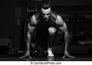 Survival Of The Fittest - Strong Muscular Men Kneeling On...