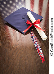 Graduation Cap and Dipoma on Table with American Flag...