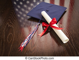 Graduation Cap and Dipoma on Table with American Flag Reflection
