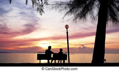 Father and Daughter Sit on the Beach against the Sunset -...