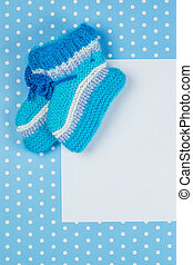 knitted baby socks and blank note on blue polka dot background