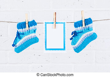 knitted baby socks and blank note hanging on clothesline...