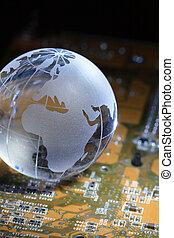 Global Technology - Close-up of glass globe lying on circuit...