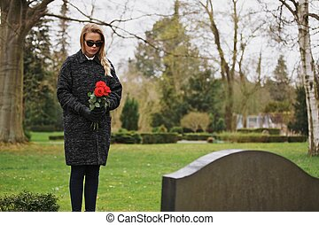 Woman grieving at cemetery holding flowers - Young woman...
