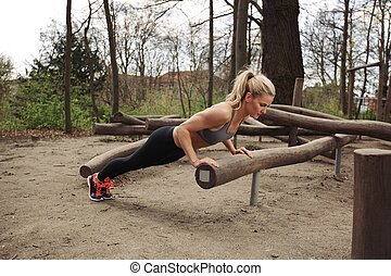 Tough young woman doing pushups on a log at park. Fit young...